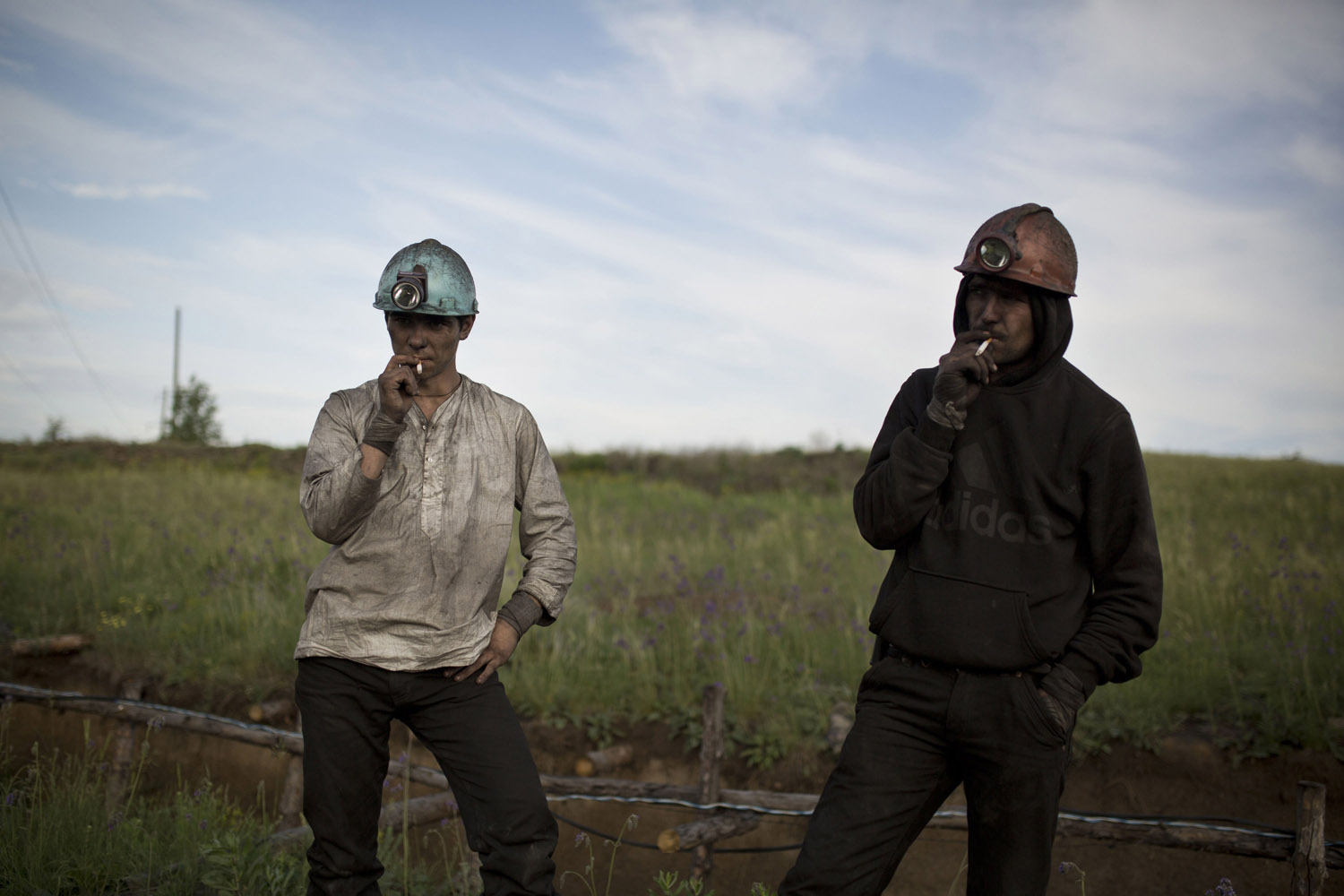 Tolek (21) and Tolek (23), smoking a cigarette after an eight-hour night shift in an illegal mine in Davidovka. The mine is located a few hundred meters from their houses.
