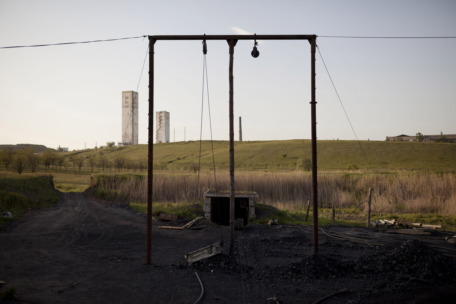 "An illegal mine in Davidovka, with the towers of the ""Glubje"" (deeper) mine rising on the horizon. Reaching 1,650 meters below the ground, the mine is the deepest in the Donbass. Many miners died in its tunnels, where temperatures can reach 55 degrees Celsius."