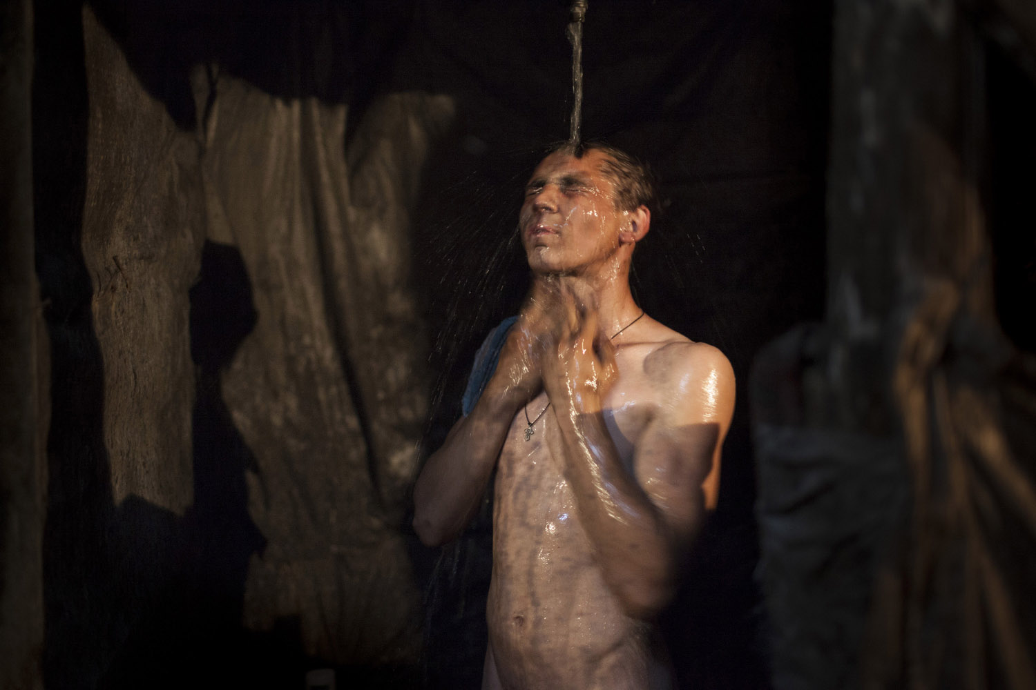 "Marek (18), taking a shower after his eight-hour night shift in an illegal mine in Davidovka. The humble conditions in which miners work today are often compared to the times of the Soviet Union, when miners were heroes ""who could even smoke where it was forbidden to do so, and the state gave them free milk to clean their lungs from the coal""."