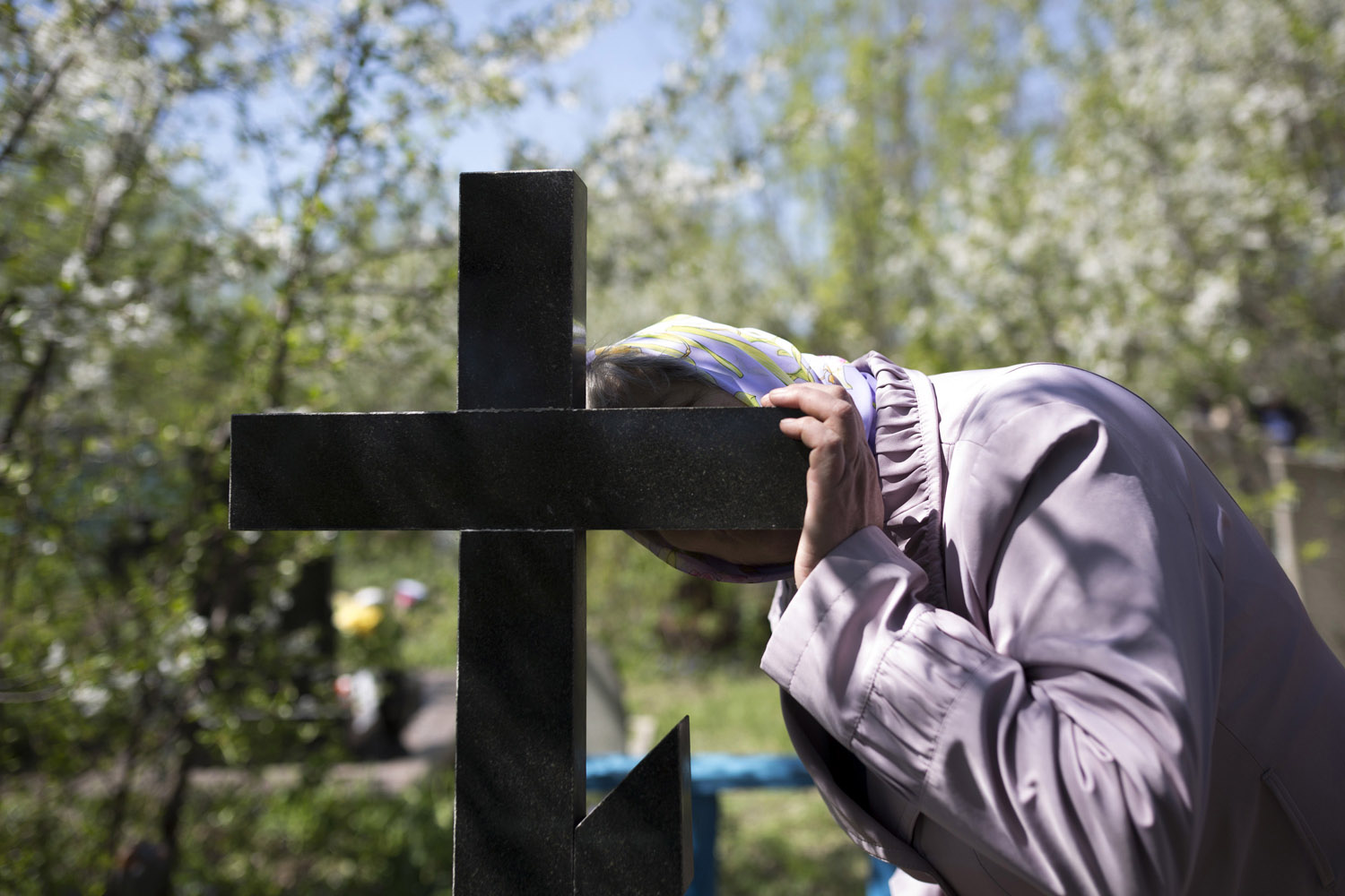The mother of Andrey Papov, who died at the age of 34 in a mining accident, kisses his grave on the first sunday after Easter, when Russian orthodox families visit their dead relatives, holding a picnic on their graves to spend some more time together.