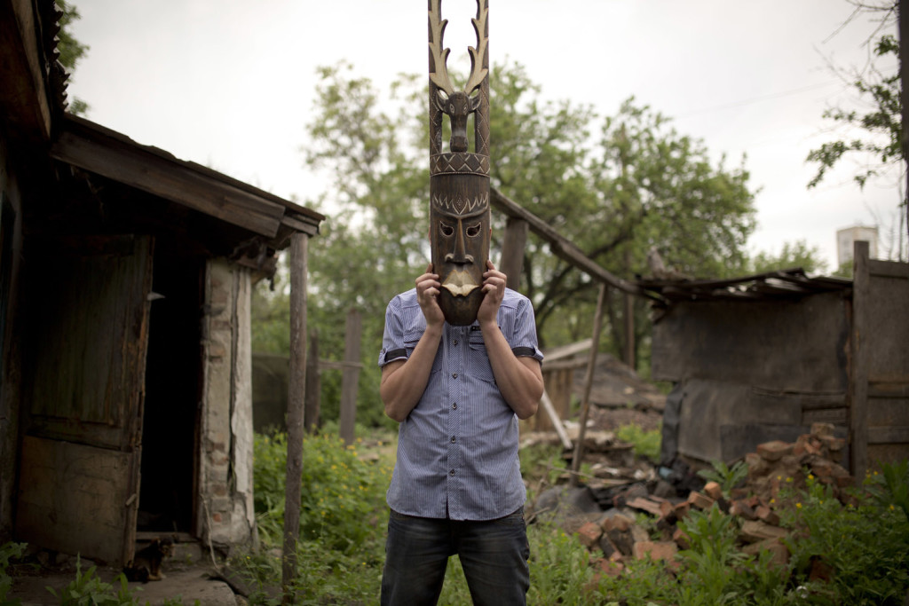 Tolek (23), playing with a mask he carved out of wood.