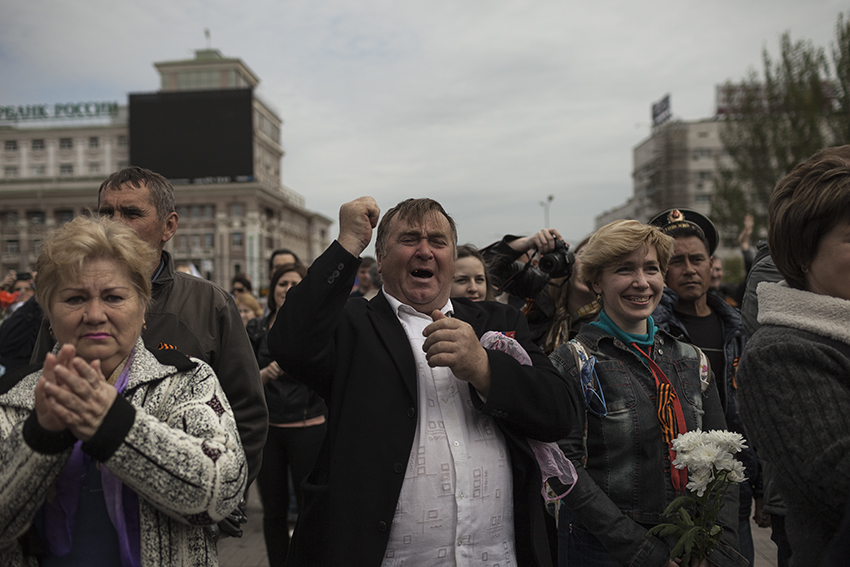 A crowd of Donetsk residents react to the Vostok Battalion parading in the city center during the Victory Day celebrations.