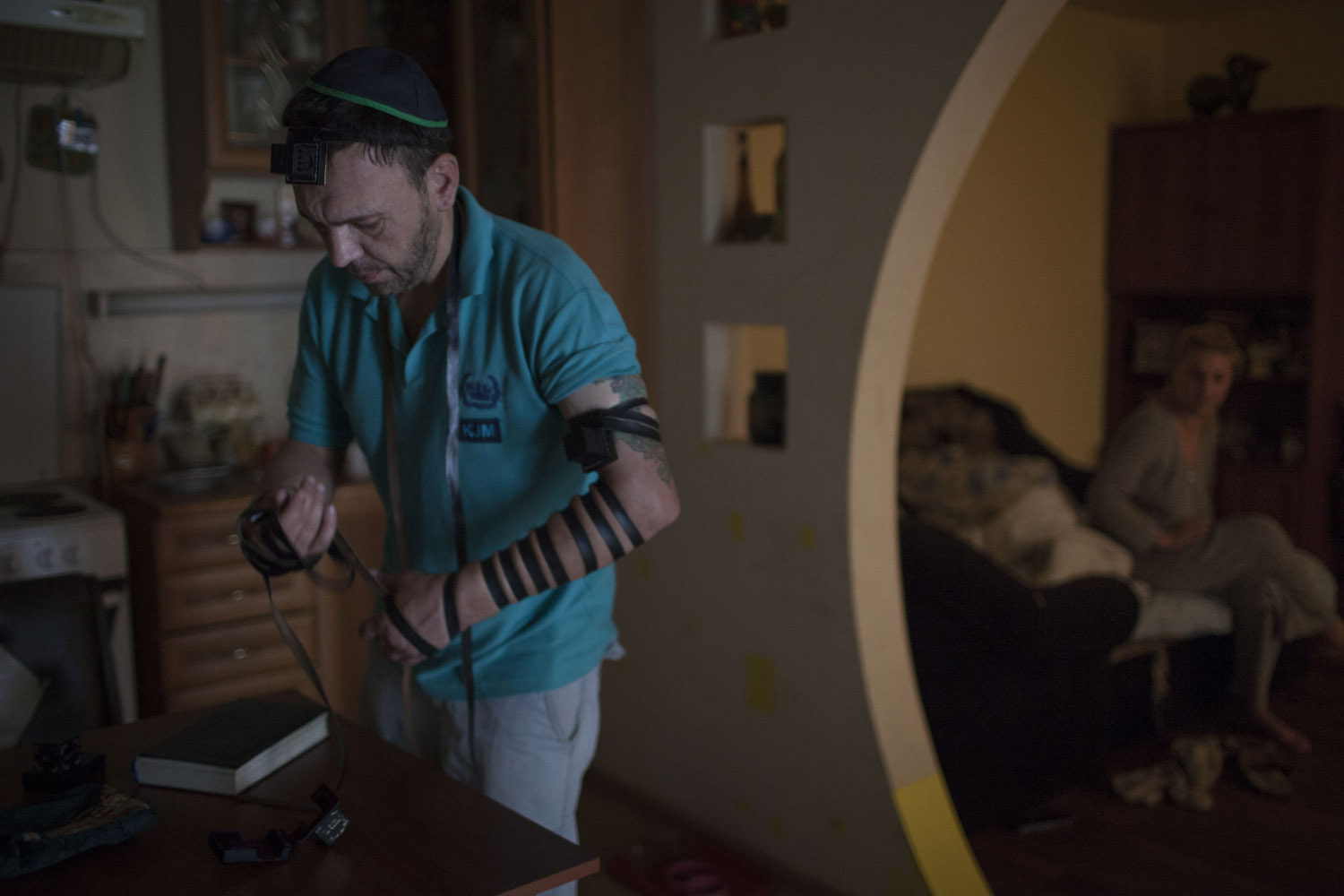 Shimon putting on tefillin for his morning prayers while his Christian wife wakes up from bed. His mother told him he was Jewish only after he grew up, so he did not get any Jewish education, but he's trying his best to keep the traditions.
