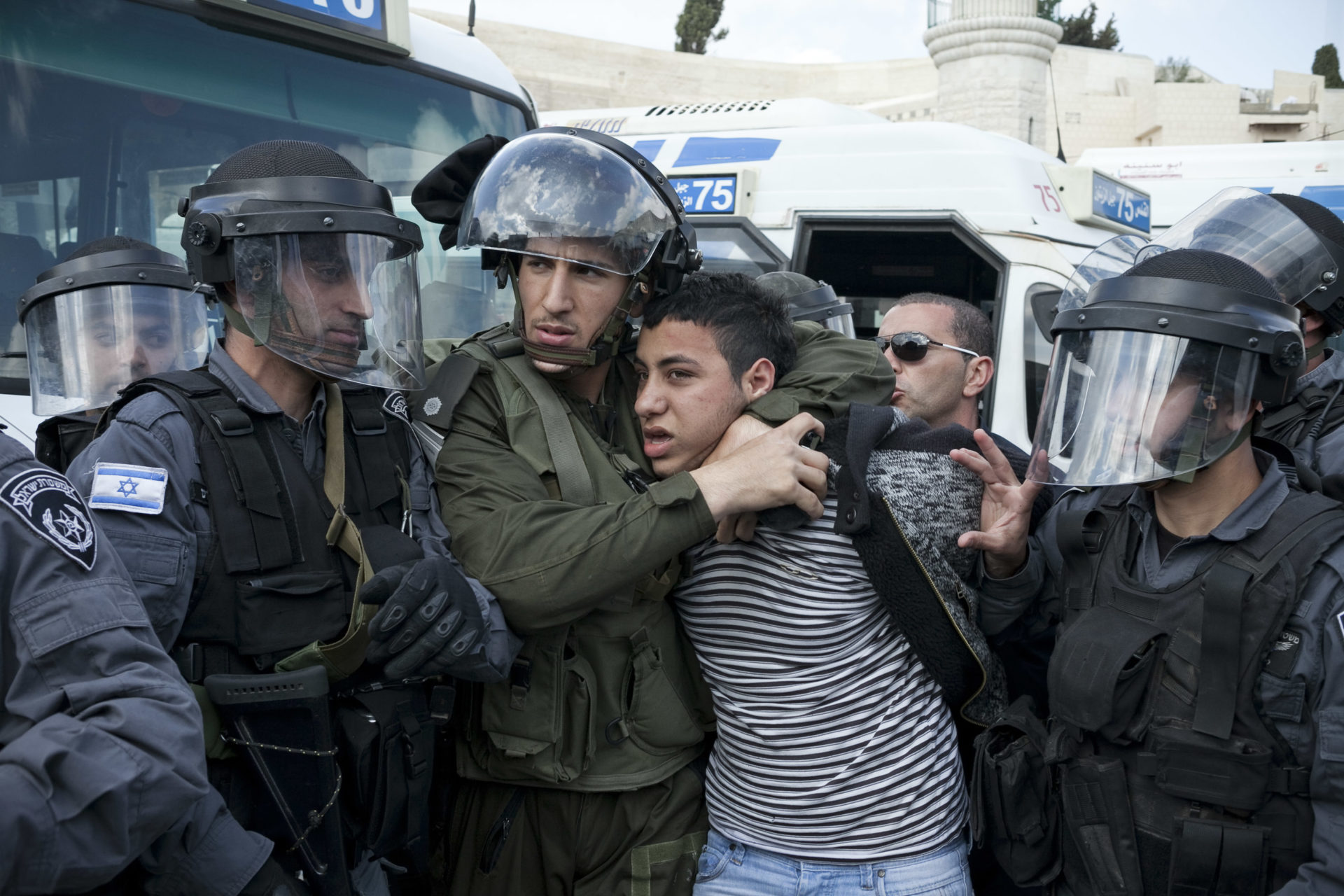 Israeli policemen carry out an arrest after the violent dispersal of a peaceful protest against the occupation. The arrestee signalled to be deaf and mute, and denied categorically to have thrown any stones, or even taken part in any protest.