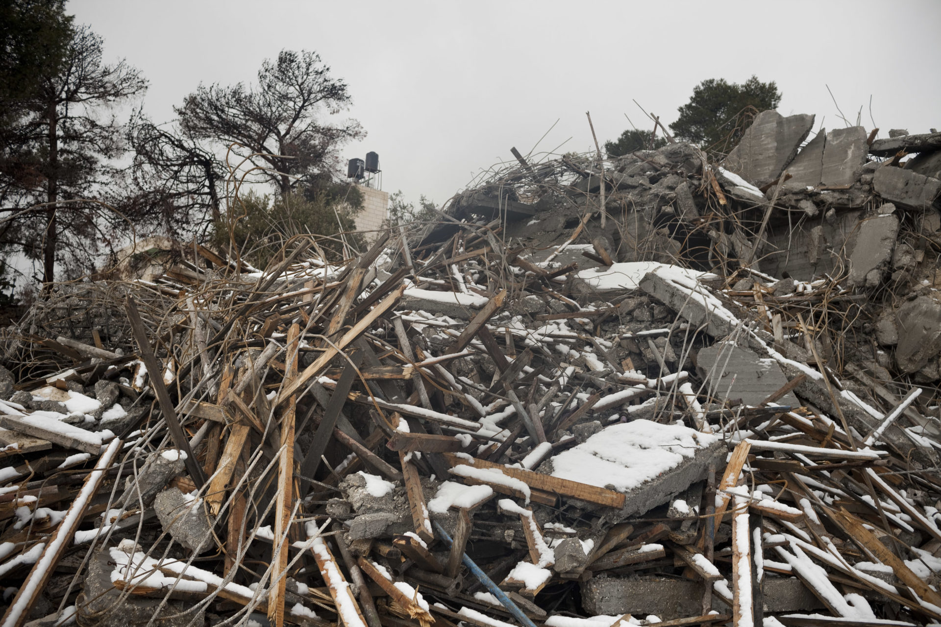 Snow falls of the ruins of a house demolished by the municipality of Jerusalem in Ras al-Amoud, a few hundred meters down the road from the Mount of Olives.