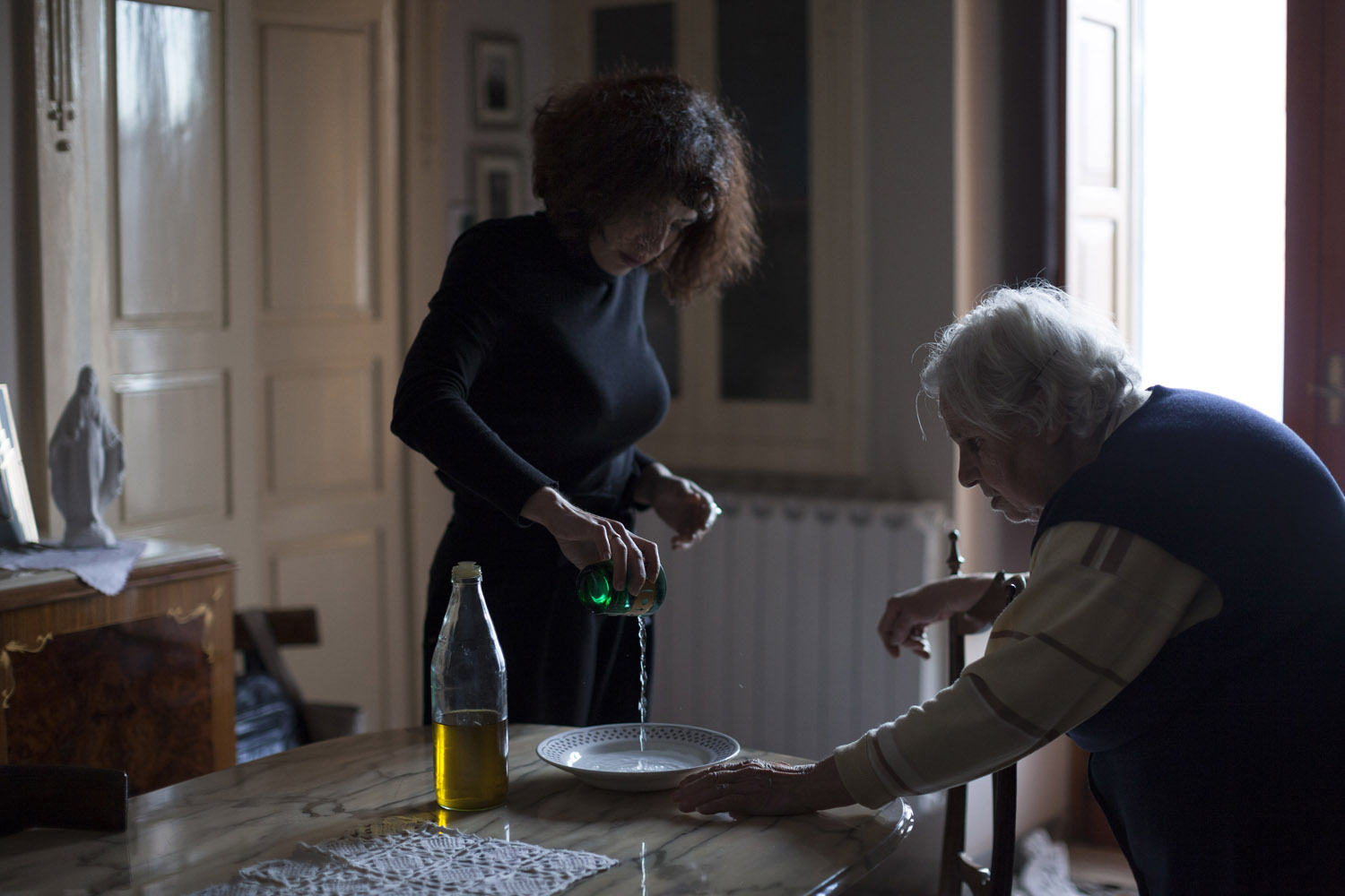 "In the village of Locorotondo, Sara and her grandmother prepare for the traditional ritual to ward off the ""malocchio"" (the evil eye), which consists of pouring drops of olive oil on water and watching how they behave. Such rituals are very common throughout South Italy, and often have olive oil as their central element. (2017)"
