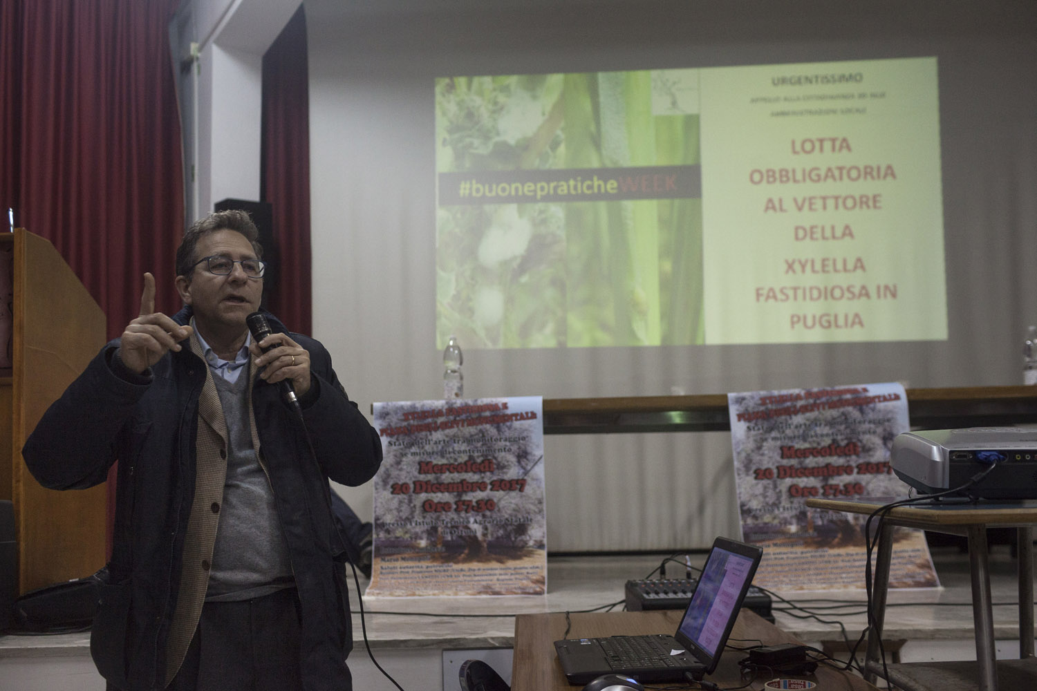 "A researcher from the CNR (National Research Council) of Bari explaining the authorities' containment plans of the outbreak and the ""obligatory measures against the vector of Xylella fastidiosa in Puglia"" at a public meeting in Ostuni. (2017)"