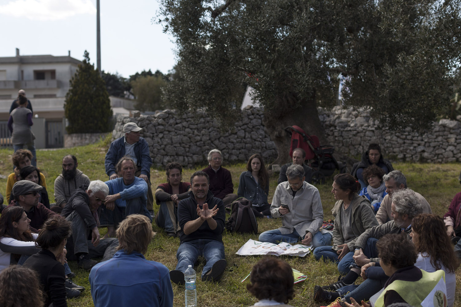 Activists discuss the crisis at the end of a demonstration against the eradication of olive trees in Cisternino, in an olive grove marked for destruction under the authorities' containment plans. According to the activists, these trees do not show signs of the disease, and if they are really infected by Xylella fastidiosa, they should then be studied as an example of coexistence with the bacteria. (2018)