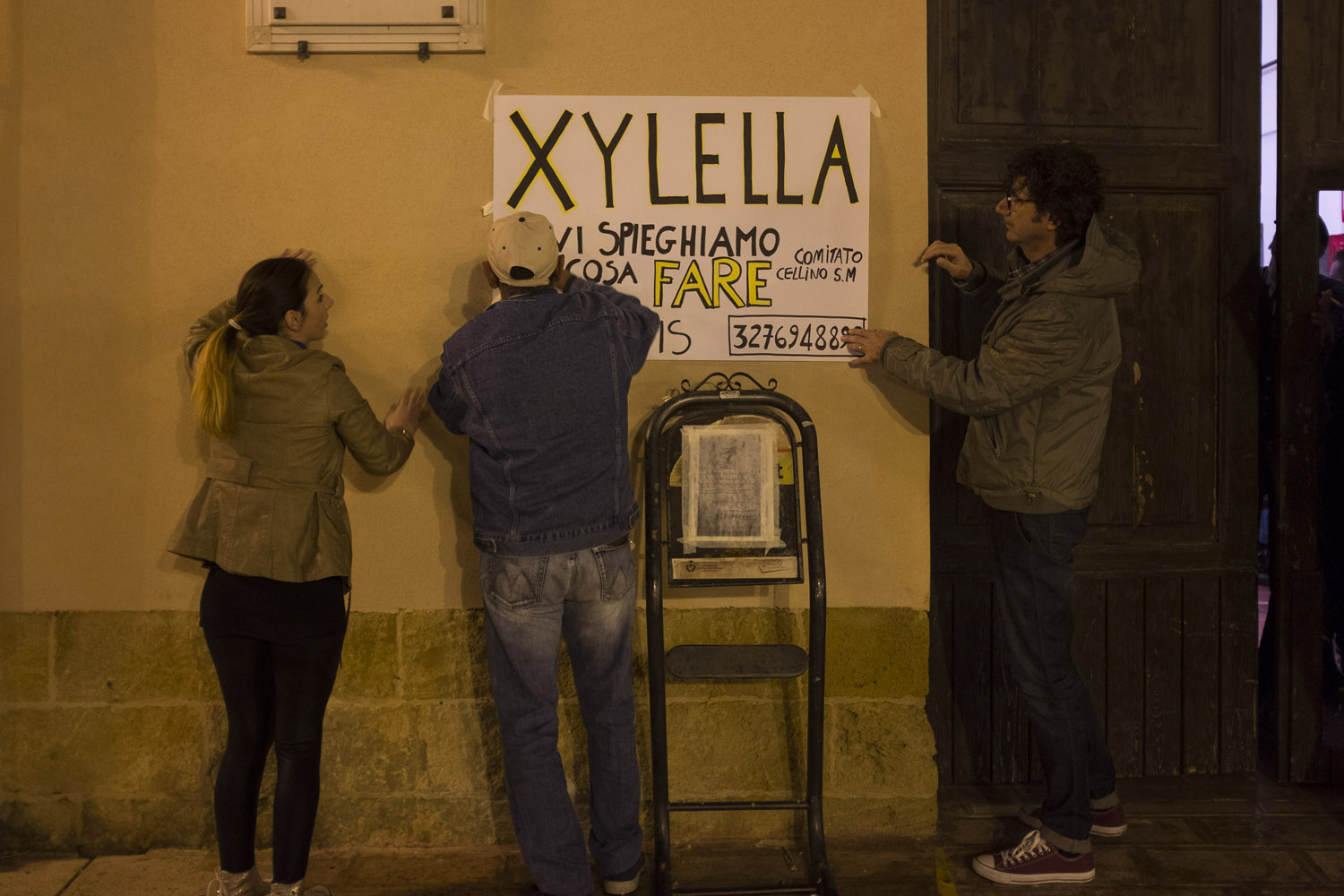 "Activists preparing for a public meeting titled ""Xylella, we explain you what to do"" in Cellino San Marco, meant to mobilize local farmers against the authorities' plans to eradicate olive trees in the area in order to contain the Xylella fastidiosa outbreak, and support them in their appeals against the eradication orders. (2015)"