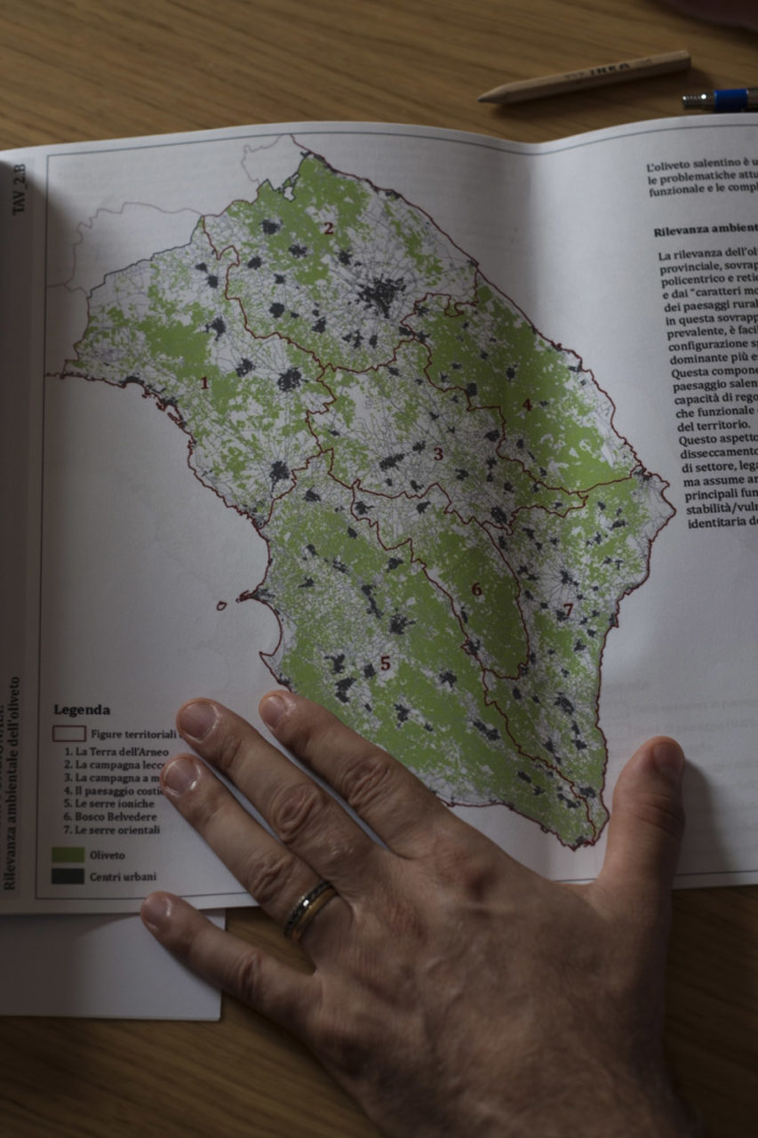 Cristian Casilli, member of the Regional Council for the Five Stars Movement, showing his party's in-depth report on the geographical aspects of Xylella fastidiosa, with the green areas showing the vast amount of Salento's land occupied by olive groves. (2019)