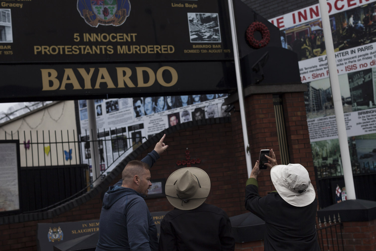 A tourist guide showing the memorial for the victims of the Bayardo bombing, in which a pub at the hearth of the Protestant area of Shankill Road was blown up by the IRA (Irish Republican Army, the main Catholic paramilitary organization) a few minutes after a gathering of loyalist paramilitaries had taken place on its first floor. The visible traces of the conflict such as political  murals or the Peace Lines have become tourist attractions of sorts, with organized tours and specialized guides, who often are former paramilitaries themselves.
