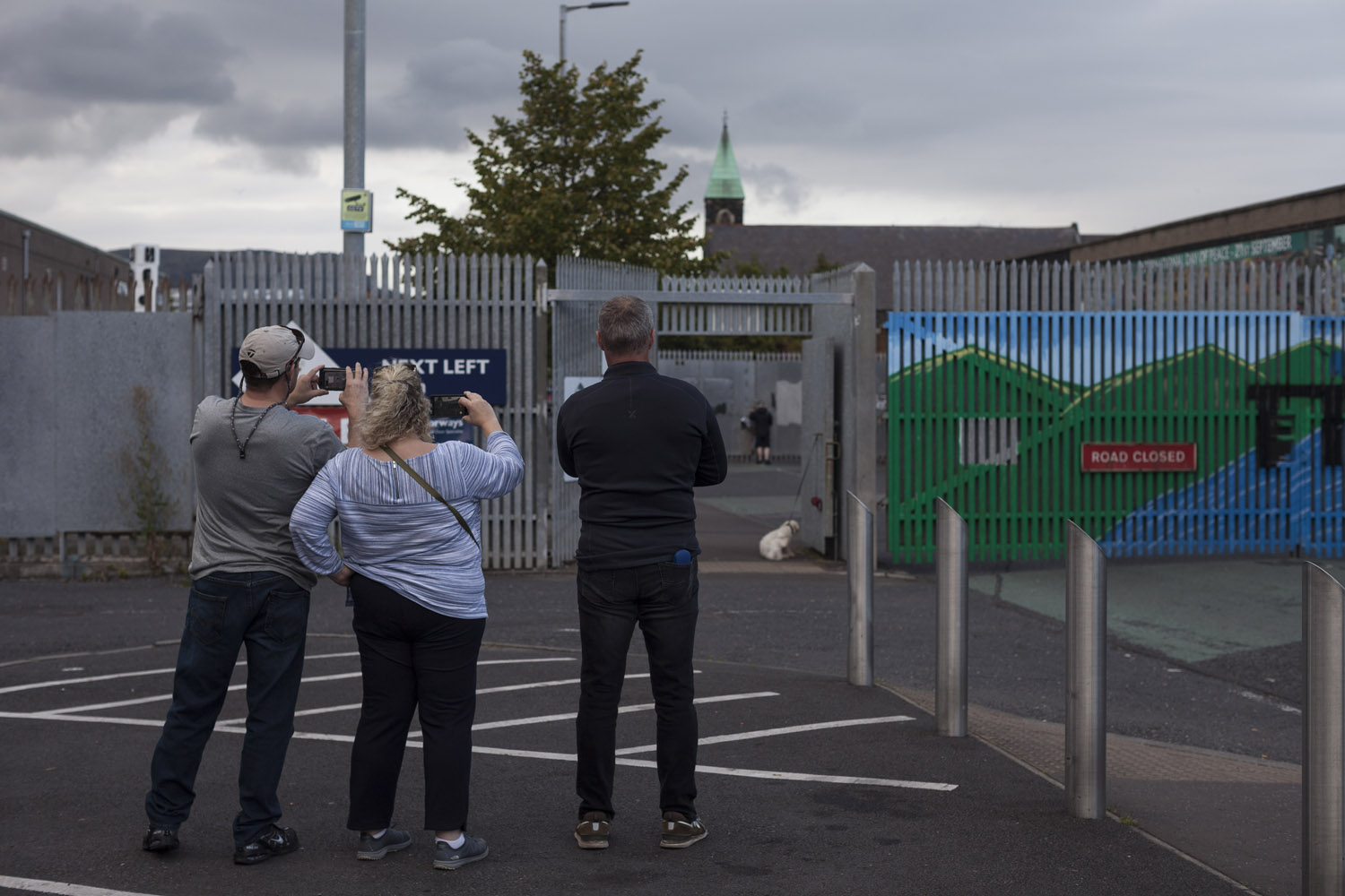 Tourist take photos as the gates of one of Belfast's Peace Lines is closed in the evening.