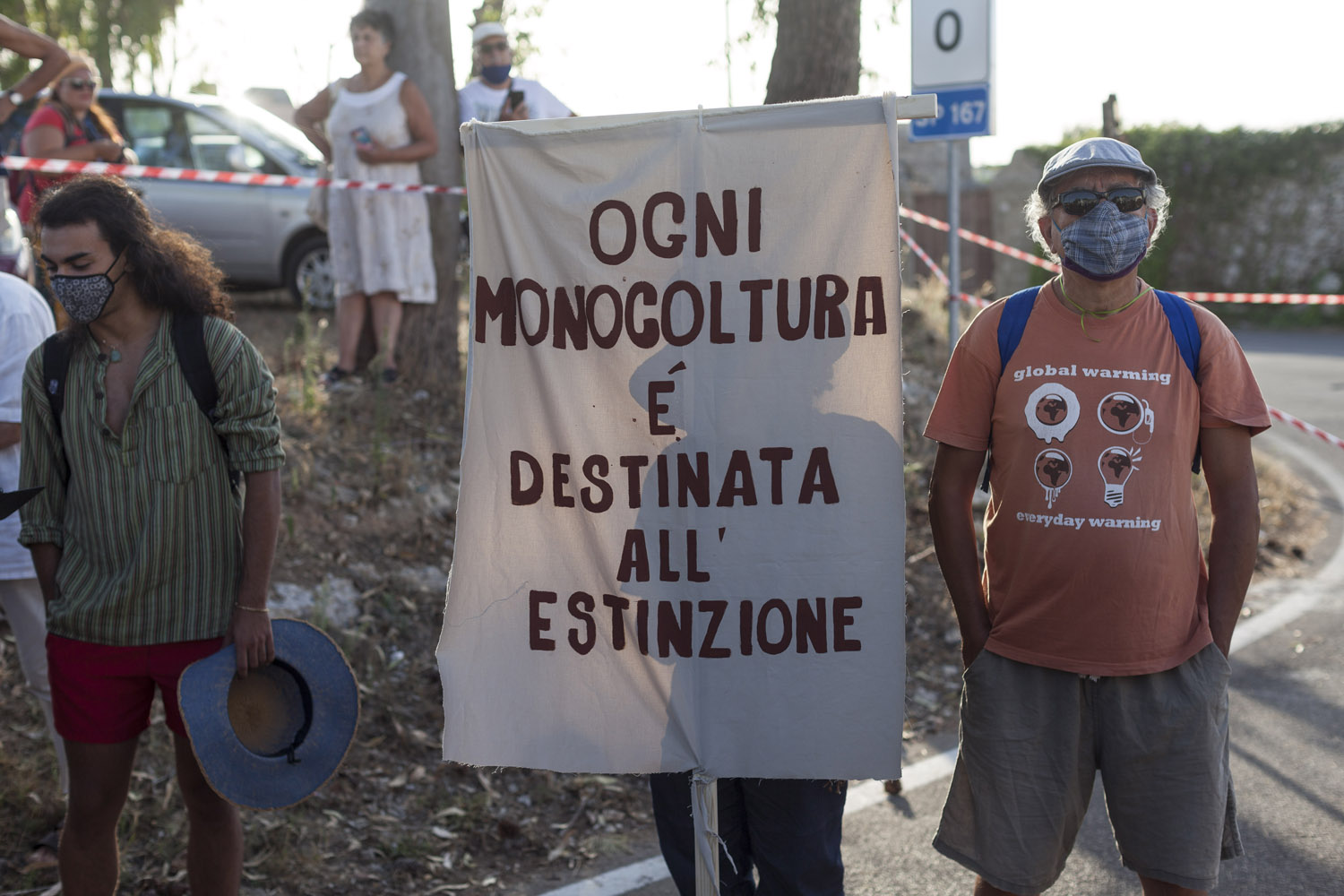 """A banner reads """"every monoculture is destined for extinction"""" at the """"Notte Verde"""" of Castiglione d'Otranto, a yearly gathering of environmental activists and farmers. This year, the theme was """"reforestation"""", in a sign of how the death of the olive trees is finally being accepted by the population, with the debate moving on what to do after the trees are dead, and an entire territory must be re-imagined."""